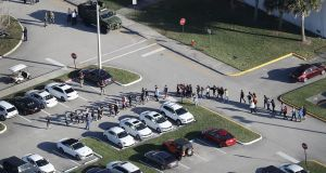 People are brought out of the Marjory Stoneman Douglas High School in Florida after a multiple-fatality shooting at the school. Photograph: Joe Raedle/Getty Images