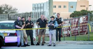 A group of police officers stand guard in front of the side entrance of the Marjory Stoneman Douglas High School. Photograph: Cristobal Herrera/EPA