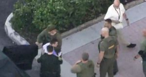 Police escort a suspect into the Broward Jail after checking him at the hospital following a shooting incident at a Florida High School. Photograph: Reuters
