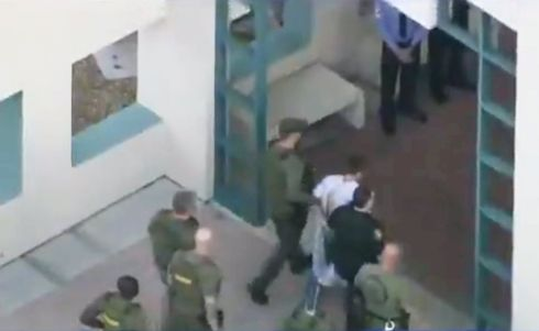 Police escort a suspect after checking him at hospital following a mass shooting at Marjory Stoneman Douglas High School in Parkland, Florida. Video iamge: WSVN.com via Reuters