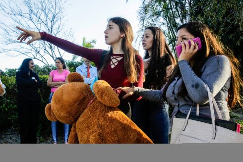From left: Nicole, Dalilia and Anna search for their parents after the mass shooting at the Marjory Stoneman Douglas High School in Parkland, Fla., Feb. 14, 2018. At least 17 people were killed Wednesday at this school about an hour northwest of Miami, law enforcement officials said. A suspect, a former student, is in custody. (Saul Martinez/The New York Times)