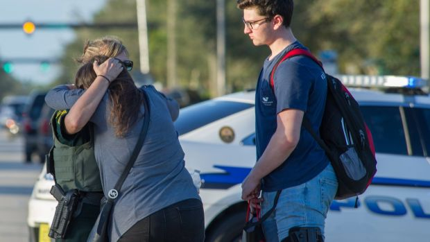 A woman is comforted by police after a shooting at Marjory Stoneman Douglas High School in Florida. Photograph: EPA