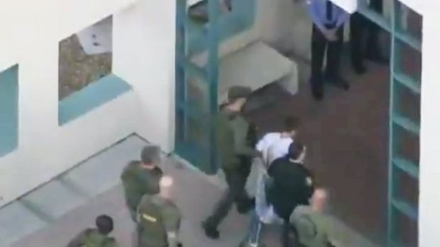 Police escort a suspect into the Broward Jail after checking him at the hospital following the shooting at Marjory Stoneman Douglas High School in Florida. Photograph: Reuters