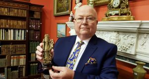 George Mealy holding the carved rhino horn figurine