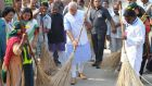 Indian prime minister Narendra Modi (centre) with other workers cleaning a road, in New Delhi, India in 2014. Photograph: Indian Press Information Bureau/EPA