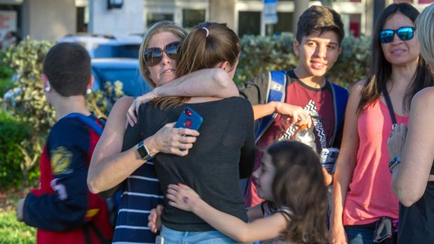Students are comforted by parents and family after a shooting at Marjory Stoneman Douglas High School in Parkland, Florida. Photograph: Georgio Viera/EPA