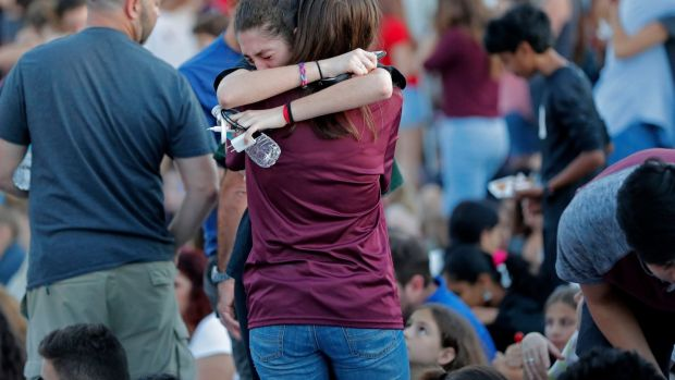People hug one another before the start of a candlelight vigil for the victims of the shooting. Photograph: Gerald Herbert/AP