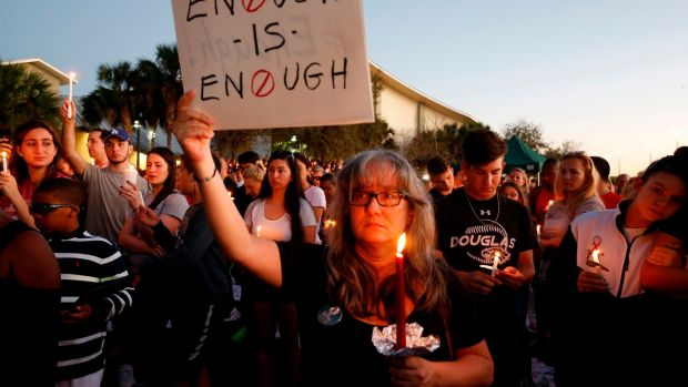 Mourners stand during a candlelight vigil for the victims of Marjory Stoneman Douglas High School shooting in Parkland, Florida. Photograph: Rhona Wise/AFP