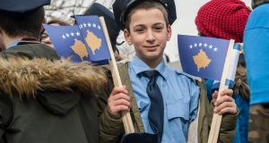 A boy dressed as a police officer holding Kosovo flags in Pristina on the eve of celebrations for the 10th anniversary of Kosovo independence. Photograph: Getty Images