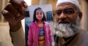 Mohammed Amin shows a picture of his seven year-old daughter, Zainab Ansari in Kasur, Pakistan. Photograph: BK Bangash/AP