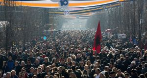 An Albanian flag is carried as thousands of people walk down the main pedestrian zone in Pristina,  on Saturday, the 10th anniversary of Kosovo's independence. Photograph: Visar Kryeziu/AP