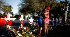 Adin Chistian (16), student of the Marjory Stoneman Douglas High School, with his mother, next to the crosses and Stars of David to commemorate Parkland, Florida victims. Photograph: Reuters