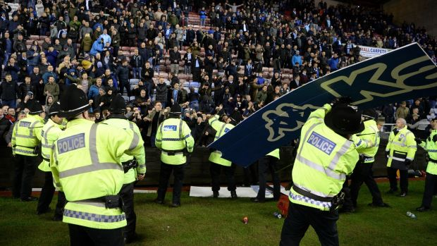 An advertising board is thrown at police as they attempt to prevent a pitch invasion after the FA Cup match between Wigan Athletic and Manchester City at DW Stadium. Photograph: Gareth Copley/Getty Images