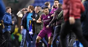 Sergio Agüero of Manchester City is surrounded by fans as he attempts to leave the pitch after the FA Cup match against  Wigan Athletic  at DW Stadium. Photograph: Gareth Copley/Getty Images