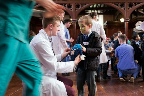 TEDDY BEAR HOSPITAL: Aidan Cotter of Glasheen Boys NS (also known as Scoil Mhuire Gan Smal) explains to UCC medical student Thomas Twohill how his teddybear broke his leg. The two met at the Teddy Bear Hospital, run by the UCC Medical Society (MedSoc), which opens annually as a community outreach activity and aims to reduce the fear many children have around doctors. Photograph: Clare Keogh