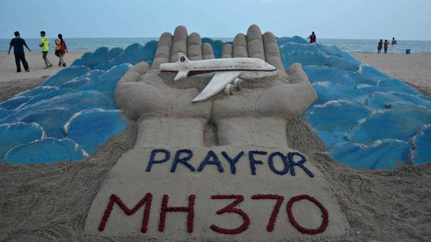 Beachgoers walk past a sand sculpture made by Indian sand artist Sudersan Pattnaik with a message of prayers for the missing Malaysian Airlines flight MH370. Photograph: Asit Kumar/AFP/Getty Images