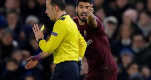 Referee Cuneyt Cakir shows a yellow card to an indignant Luiz Suarez during Barcelona's Champions League clash against Chelsea at Stamford Bridge. Photograph: Eddie Keogh/Reuters