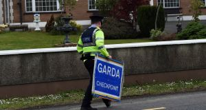 A Garda removes a  checkpoint sign at the border between counties Armagh and  Louth, during a visit by EU chief negotiator for Brexit Michel Barnier last May. Photograph: Reuters/Clodagh Kilcoyne