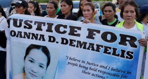 Residents display placards as they wait for the arrival of the body of Joanna Demafelis, the  Filipina domestic worker who was killed and found inside a freezer in Kuwait, in her hometown in Iloilo province in the Philippines. Photograph: Reuters