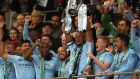 Vincent Kompany of Manchester City lifts the trophy and celebrates with team-mates after winning the Carabao Cup Final  against Arsenal at Wembley Stadium. Photograph:  Catherine Ivill/Getty Images