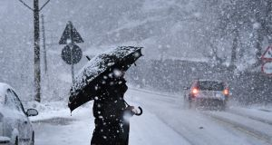 A man walks with an umbrella under heavy snow in Pogradec, Albania. Photograph: Gent Shkullaku/AFP/Getty Images