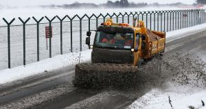 A snow plough clears a road at Dublin Airport today. Photograph: Brian Lawless/PA Wire