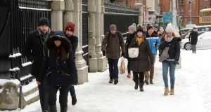 Walking in the snow in Dublin city centre on Thursday. Many theatres, cinemas and museums have cancelled events. Photograph: Dara Mac Dónaill/The Irish Times