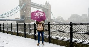 A tourist stops in the snow past Tower Bridge,  London, Britain. Photograph: Will Oliver/EPA