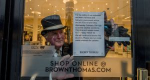 Brown Thomas concierge  Jim Kearns puts a sign up in the Dublin city-centre store announcing its temporary closure due to adverse weather. Photograph: Brenda Fitzsimons