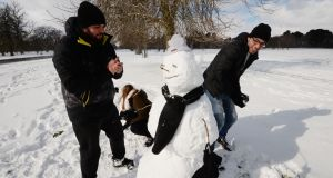 Izabella Mimic, Bruno Felippe and Pedro Caldas from Brazil in Snow for the first time in their lives build a snowman in the Phoenix Park. Photograph: Alan Betson/ The Irish Times