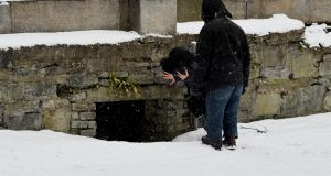 Members of the Safetynet / Simon Community attempt to coax a homeless person living in a hole in a wall near a waterway in Dublin to accept an offer of accommodation on Thursday. Photograph: Alan Betson/The Irish Times
