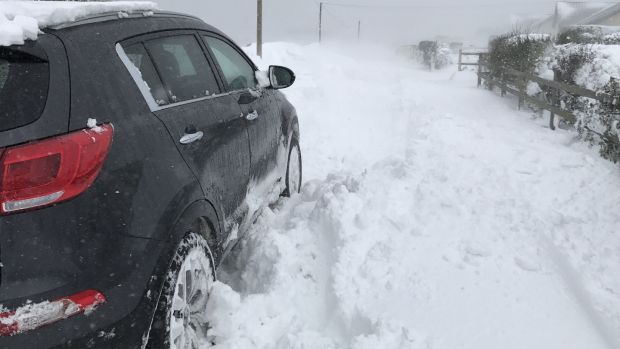 A car tries to navigate a snow-covered road in Kinsale, Co Cork, on Thursday. Photograph: Sarah and Cillian Fitzgerald