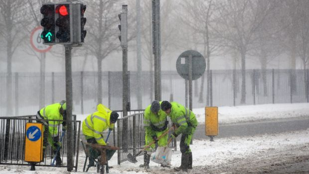 Workers clear and grit paths in Blanchardstown on Thursday afternoon. Photograph: Colin Keegan/Collins