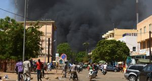 Black smoke rises as the capital of Burkina Faso comes under multiple attacks. Photograph: Ahmed Ouoba/AFP/Getty Images