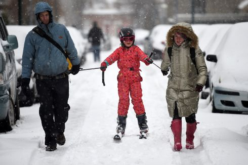Parents use a ski to go for a walk with their child after schools closed due to adverse weather conditions in Dublin, Ireland, March 2nd.  Photograph: Clodagh Kilcoyne / Reuters