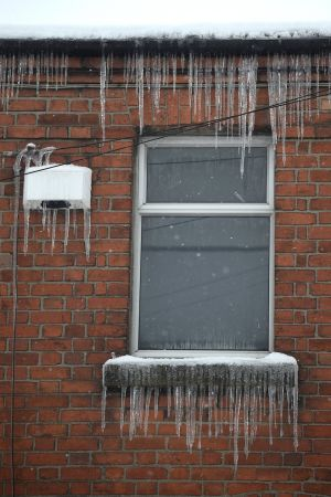 Icicles are seen hanging from a window and house alarm in Dublin. Photograph: Clodagh Kilcoyne / Reuters