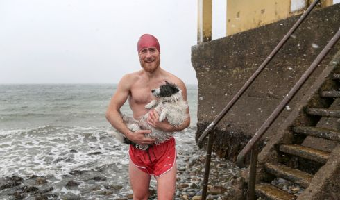 Richard McCurry from Mervue in Galway and his dog after their swim in the snow at Blackrock in Salthill Co Galway on Friday.  Photograph: Joe O'Shaughnessy
