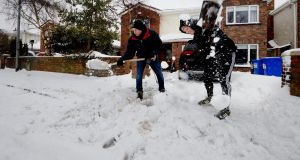 John Finnerty and John Finnerty jr clearing snow from their driveway in Dunboyne, Co Meath on Saturday. Photograph: Alan Betson
