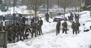 Irish Defence Forces cadets help clean up Sallins, Co Kildare: business groups have estimated the cost of the severe weather at over €100 million. Photograph:  Niall Carson/PA