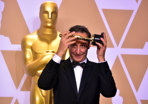 "French composer Alexandre Desplat poses in the press room with the Oscar for Best Original Score for ""The Shape of Water,"" . Photograph: Frederick Brown / Getty"