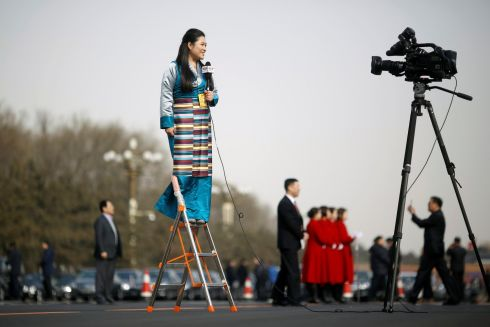 A journalist reports on a ladder outside the Great Hall of the People during the opening session of the National People's Congress in Beijing, China. Photograph: Thomas Peter/Reuters