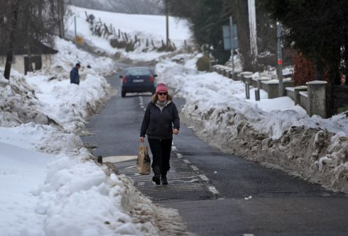 A woman ventures along the road with snow piled high at the edge of the road in Brittas, Co Wicklow, this afternoon. Photograph: Colin Keegan/Collins