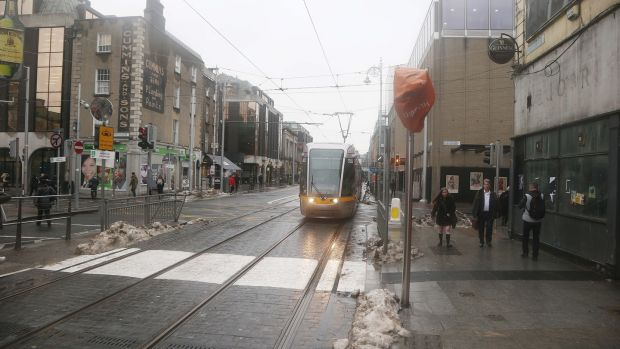 Snow melts on Abbey Street, Dublin city centre, as people return to their daily commute on Monday. Photograph: Collins