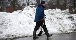 A man walks past cleared snow in Dublin on Sunday. Photograph: Clodagh Kilcoyne/Reuters