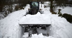 Army Private Patrick Macken clears snow with a mechanical digger to make a path to Thomas Jones' farm in Blessington, Co Wicklow. Photograph: Reuters