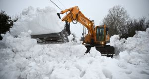 A  digger clears snow from a road in Kilteel, Co Kildare on Monday. Photograph: Reuters