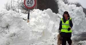 A resident walks home with her groceries along a snow-covered road in Kilteel, Co Kildare. Photograph: Reuters/Clodagh Kilcoyne