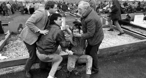 An injured man is aided by mourners, including Martin McGuinness, left, at Milltown cemetary in 1978. Photograph: David Jones/PA Archive/PA Images