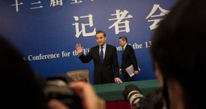 China's Foreign Minister Wang Yi waves to photographers as he arrives at a press conference during the First Session of the 13th National People's Congress in Beijing on Thursday. Photograph: Getty Images