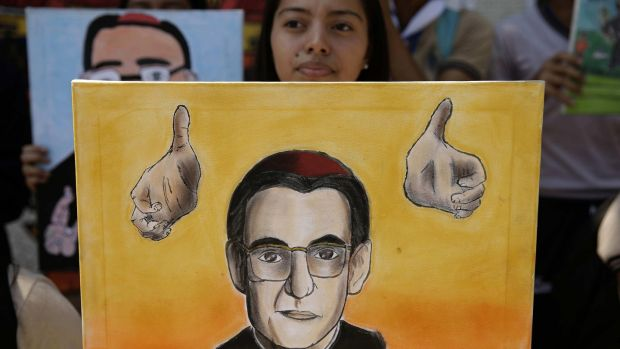 A youth holds a portrait of Archbishop Oscar Romero after the Vatican's announcement that he will be canonised. The archbishop was assassinated in El Salvador in 1980. Photograph: Rodrigo Sura/EPA